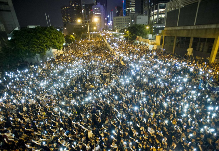 Protestors and student demonstrators hold up their cellphones in a display of solidarity during a protest outside the headquarters of Legislative Council in Hong Kong on September 29, 2014. Hong Kong has been plunged into the worst political crisis since its 1997 handover as pro-democracy activists take over the streets following China's refusal to grant citizens full universal suffrage. (Xuame Olleros/AFP/Getty Images)