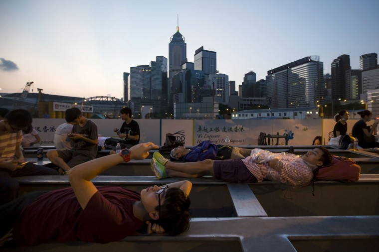 Pro-democracy protesters rest on girders near a construction site during a rally outside the government headquarters in Hong Kong early September 28, 2014. Violent clashes between Hong Kong riot police and students galvanized tens of thousands of supporters for the city's pro-democracy movement and kick-started a plan to lock down the heart of the Asian financial centre early on Sunday. (Tyrone Siu/Reuters)