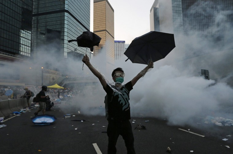 A protester (C) raises his umbrellas in front of tear gas which was fired by riot police to disperse protesters blocking the main street to the financial Central district outside the government headquarters in Hong Kong, September 28, 2014. Hong Kong police used tear gas for the first time on Sunday to disperse pro-democracy protests and baton-charged the crowd blocking a key road in the government district after Hong Kong and Chinese officials warned against illegal demonstrations. (Tyrone Siu/Reuters)