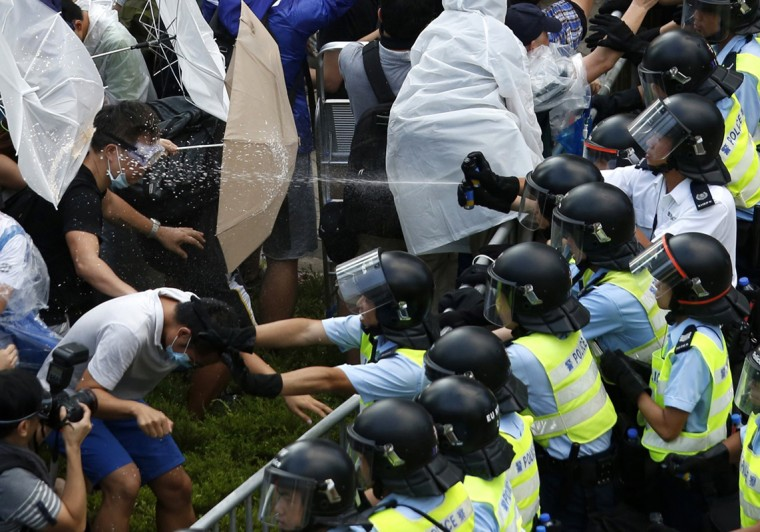 Riot police use pepper spray as they clash with protesters, as tens of thousands of protesters block the main street to the financial Central district outside the government headquarters in Hong Kong September 28, 2014. The leader of a Hong Kong movement seeking greater democracy announced in the early hours of Sunday the launch of a campaign to blockade the heart of the financial centre to demand greater freedoms in the former British colony. (Bobby Yip/Reuters)