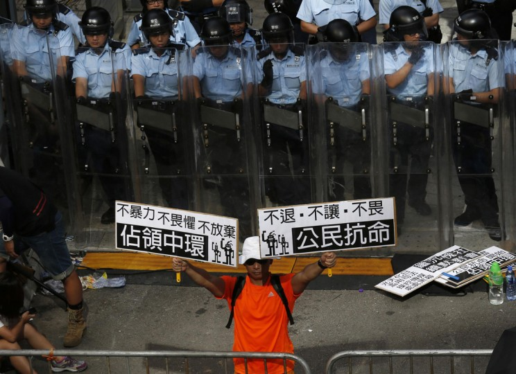 "A protester holds up placards which reads ""Occupy Central"" (L) and ""Civil Disobedience"" in front of a line of riot police outside government headquarters in Hong Kong September 27, 2014. Hong Kong riot police used pepper spray to disperse protesters around government headquarters on Saturday, fuelling tension ahead of a planned sit-in by pro-democracy activists to protest against Beijing's tightening grip on the city. (Bobby Yip/Reuters)"