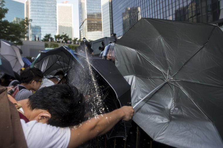 "Riot police target pro-democracy students with pepper spray after hundreds of protesters stormed into a restricted area at the government headquarters, after a rally ahead of the October 1 ""Occupy Central"" civil disobedience movement in Hong Kong September 27, 2014. Hong Kong riot police used pepper spray on Saturday to disperse dozens of students who had stormed government headquarters, but an equal number held their ground in protests against Beijing's tightening grip on the city. (Tyrone Siu/Reuters)"