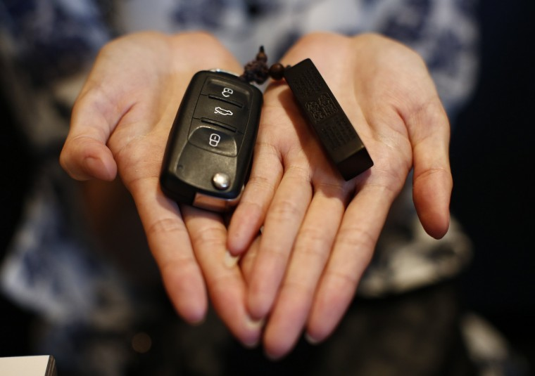 Zhang, whose husband Wang Houbin was onboard Malaysia Airlines Flight MH370 which disappeared on March 8, 2014 shows her husband's car key and key holder during an interview with Reuters in Beijing July 18, 2014. Six months after Malaysia Airlines Flight MH370, with 239 mostly Chinese people on board, disappeared about an hour into a routine journey from Kuala Lumpur to Beijing March 8, loved ones of missing passengers derive what comfort they can from what's left behind after the world's greatest aviation mystery. (Kim Kyung-Hoon/Reuters)
