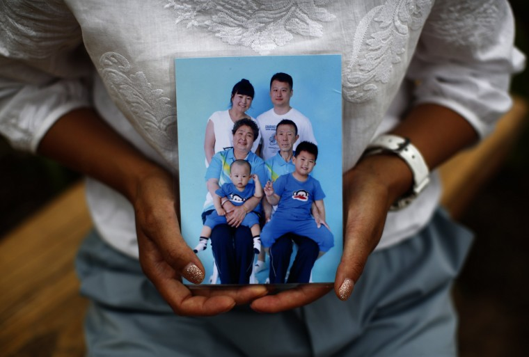 Cheng Liping, whose husband Ju was onboard Malaysia Airlines Flight MH370 which disappeared on March 8, 2014 shows a family photo featuring her missing husband (top, R) at a park near her house where she and her husband used to visit, during an interview with Reuters in Beijing July 24, 2014. Cheng said her life has been totally changed since the incident. (Kim Kyung-Hoon/Reuters)