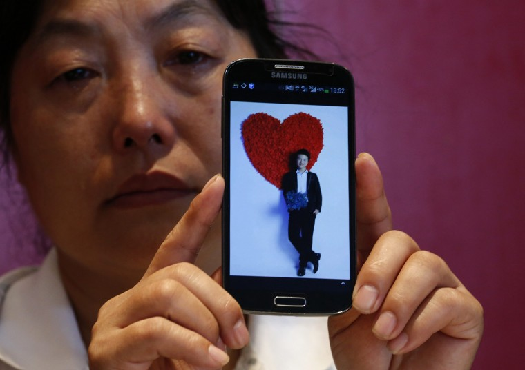 "Feng Xuehong, whose son Wang Houbin was onboard Malaysia Airlines Flight MH370 which disappeared on March 8, 2014 cries as she shows a picture of her son on her mobile phone during an interview with Reuters in Beijing July 18, 2014. In the last conversation with her son before the incident, the son said, ""Give me a hug, mom. Take care of yourself and I'll come back to see you soon."" (Kim Kyung-Hoon/Reuters)"