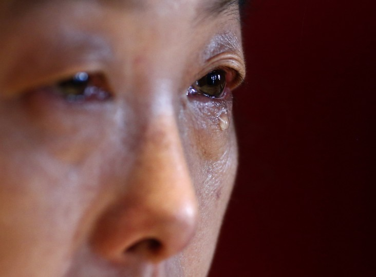 "Feng Xuehong, whose son Wang Houbin was onboard Malaysia Airlines Flight MH370 which disappeared on March 8, 2014, cries during an interview with Reuters in Beijing July 18, 2014. In the last conversation with her son before the incident, the son said, ""Give me a hug, mom. Take care of yourself and I'll come back to see you soon."" Six months after Malaysia Airlines Flight MH370, with 239 mostly Chinese people on board, disappeared about an hour into a routine journey from Kuala Lumpur to Beijing March 8, loved ones of missing passengers derive what comfort they can from what's left behind after the world's greatest aviation mystery. (Kim Kyung-Hoon/Reuters)"