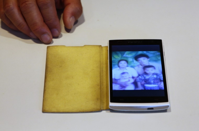 Liu Kun, whose younger brother Liu Qiang was onboard Malaysia Airlines Flight MH370 which disappeared on March 8, 2014 shows a picture of his brother (top, R) on his mobile phone during an interview with Reuters in Beijing July 18, 2014. Liu said he does not believe that the vanished plane crashed in the Indian Ocean losing all people on board. He wishes his brother and other people onboard the plane are still alive. Six months after Malaysia Airlines Flight MH370, with 239 mostly Chinese people on board, disappeared about an hour into a routine journey from Kuala Lumpur to Beijing March 8, loved ones of missing passengers derive what comfort they can from what's left behind after the world's greatest aviation mystery. (Kim Kyung-Hoon/Reuters)