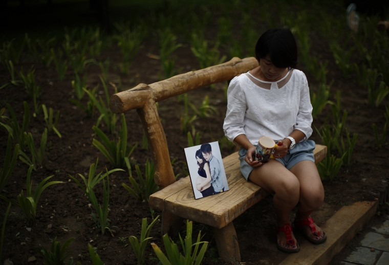 Cheng Liping, whose husband Ju was onboard Malaysia Airlines Flight MH370 which disappeared on March 8, 2014 shows a picture which features she and her husband together, and her husband's cup, at a park near her house where she and her husband used to visit during an interview with Reuters in Beijing July 24, 2014, Cheng said her life has been totally changed since the incident. Their two little sons, who don't know about this incident, keep asking her when their dad is coming back. (Kim Kyung-Hoon/Reuters)