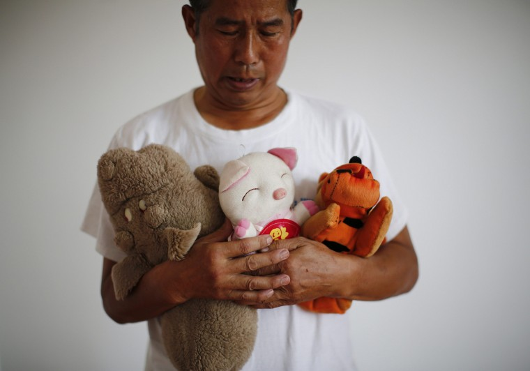 Zhang Yongli, whose daughter Zhang Qi was onboard Malaysian Airlines Flight MH370 which disappeared on March 8, 2014 looks at his daughter's plush toys as he poses for a picture, during an interview with Reuters in Beijing July 22, 2014. Zhang said this incident is disrupting the lives of he and his wife now. His wife sometimes roams several kilometers far from home because she cannot stand staying in their home from which her daughter is now absent. (Kim Kyung-Hoon/Reuters)