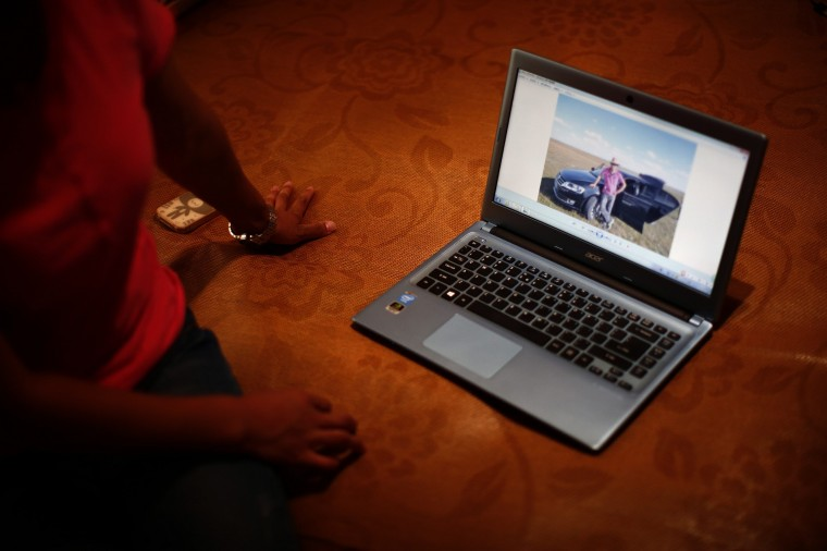 Liu, whose husband Li Zhijin was onboard Malaysia Airlines Flight MH370 which disappeared on March 8, 2014, shows her husband's picture on a laptop during an interview with Reuters in Beijing July 22, 2014. Liu said she argued with her husband in their last phone call before the incident. She could not have realised that this would be their last conversation and now that is her greatest regret. (Kim Kyung-Hoon/Reuters)