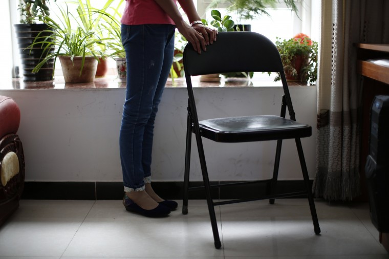 Liu, whose husband Li Zhijin was onboard Malaysia Airlines Flight MH370 which disappeared on March 8, 2014, poses with her husband's chair during an interview with Reuters in Beijing July 22, 2014. Liu said she argued with her husband in their last phone call before the incident. She could not have realised that this would be their last conversation and now that is her greatest regret. Six months after Malaysia Airlines Flight MH370, with 239 mostly Chinese people on board, disappeared about an hour into a routine journey from Kuala Lumpur to Beijing March 8, loved ones of missing passengers derive what comfort they can from what's left behind after the world's greatest aviation mystery. (Kim Kyung-Hoon/Reuters)