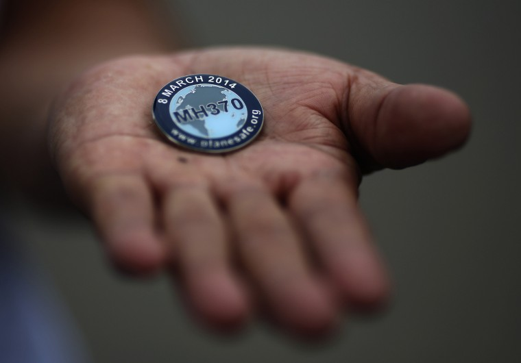 Zhang Yongli, whose daughter Zhang Qi was onboard Malaysia Airlines Flight MH370 which disappeared on March 8, 2014 shows a badge which he received from an NGO group supporting the family members of missing passengers, during an interview with Reuters in Beijing July 22, 2014. Zhang said this incident is disrupting his and his wife's lives now. His wife sometimes roams several kilometers far from home because she cannot stand staying in their home from which her daughter is now absent.Six months after Malaysia Airlines Flight MH370, with 239 mostly Chinese people on board, disappeared about an hour into a routine journey from Kuala Lumpur to Beijing March 8, loved ones of missing passengers derive what comfort they can from what's left behind after the world's greatest aviation mystery. (Kim Kyung-Hoon/Reuters)