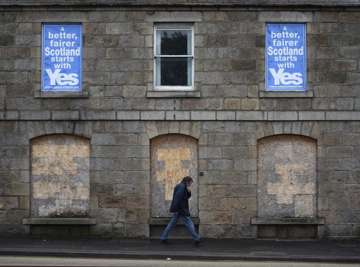 A man passes 'Yes' campaign posters as he walk along a street in Aberdeen, Scotland, on September 15, 2014. (REUTERS/Dylan Martinez)