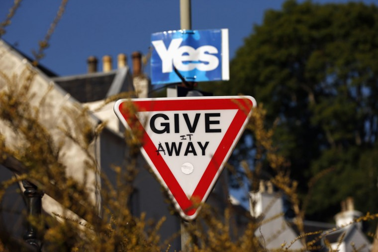 A vandalized road sign displays campaign graffiti in the town of Portree on the Isle of Skye on September 17, 2014. (REUTERS/Cathal McNaughton)