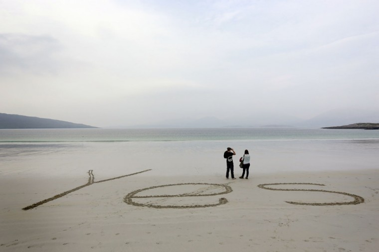 "The word ""Yes"" is scrawled on the sand as people look out over the bay at Luskentyre beach on the Isle of Harris in the Outer Hebrides on September 12, 2014. (REUTERS/Cathal McNaughton)"