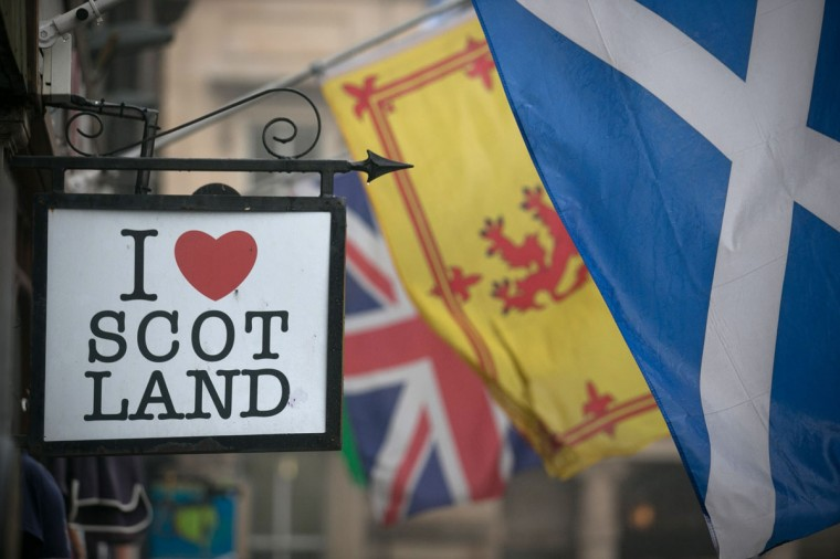 The Saltire flag flies next to the Royal Standard of Scotland and the Union Flag above a gift shop in central Edinburgh on September 19, 2014 in Edinburgh, Scotland. (Photo by Matt Cardy/Getty Images)