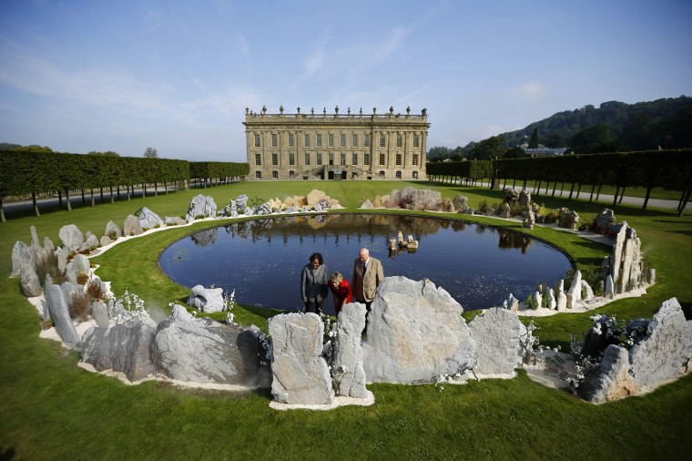 "The Duke and Duchess of Devonshire look at a piece by Chinese artist Xu Bing (L) entitled ""Tao Hua Yuan: A Lost Village Utopia"" during the Beyond Limits selling exhibition at Chatsworth House in central England September 4, 2014. (Darren Staples/Reuters)"