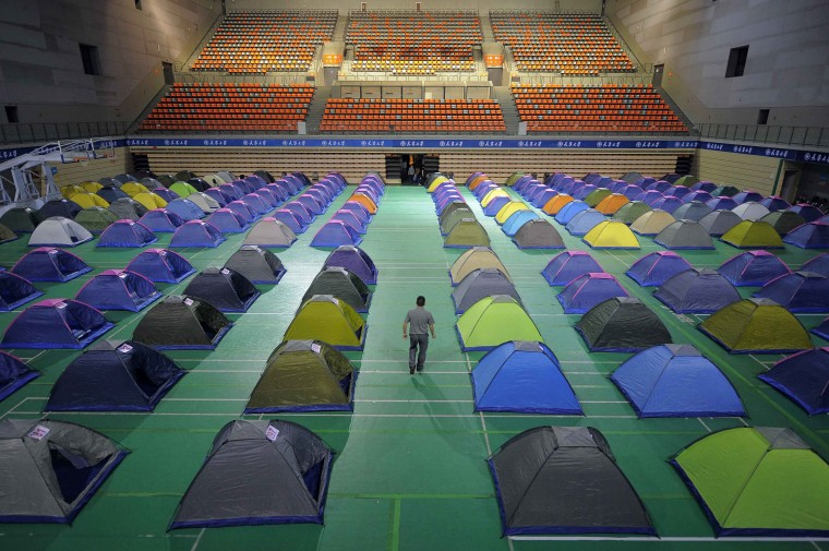 A man walks amidst tents set up on the floor of a gymnasium for parents of freshmen students at Tianjin University in Tianjin municipality, September 3, 2014. The university set up at least 270 tents in the gymnasium for the parents to stay overnight for free, local media reported. Picture taken September 3, 2014. (Stringer/Reuters)