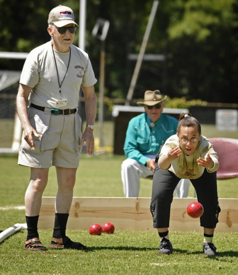 Senior volunteer Bob Thomas, left, cheers on teammate Aisha Polk, right, as she throws the ball during a bocce game. Their team won the gold medal for winning two matches in the senior unified bocce tournament of the 2010 Special Olympics Maryland Summer Games at Towson University. (Kenneth K. Lam/Baltimore Sun)