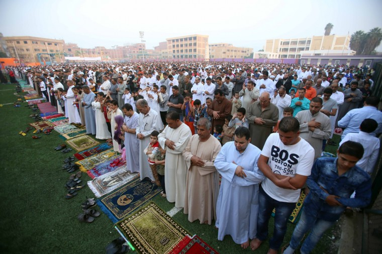 Egyptian Muslims pray on the first day of Eid al-Adha, or the Festival of Sacrifice, which marks the end of the Hajj pilgrimage to Mecca and commemorates Prophet Abraham's readiness to sacrifice his son to show obedience to God, on 4 October 2014 in the Baragil village in the province of Giza. (Mohamed El-Shahed/Getty Images)