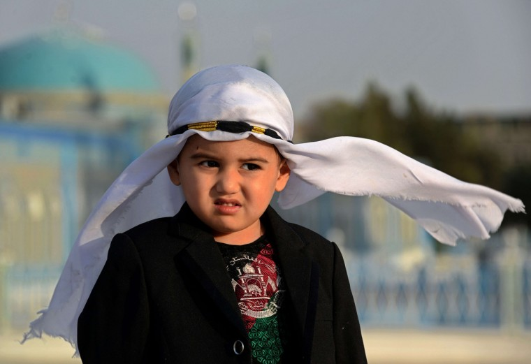 "An Afghan boy looks on as he wears new clothes on the occasion of the Eid al-Adha festival in Mazar-i-sharif on October 4, 2014. Afghans started celebrating Eid al-Adha or ""Feast of the Sacrifice"", which marks the end of the annual hajj or pilgrimage to Mecca and is celebrated in remembrance of Abraham's readiness to sacrifice his son to God. (Farshad Usyan/Getty Images)"