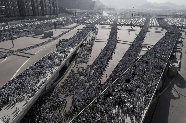"""Muslim pilgrims arrive to throw pebbles at pillars during the """"Jamarat"""" ritual, the stoning of Satan, in Mina near the holy city of Mecca, on October 4, 2014. Pilgrims pelt pillars symbolizing the devil with pebbles to show their defiance on the third day of the hajj as Muslims worldwide mark the Eid al-Adha or the Feast of the Sacrifice, marking the end of the hajj pilgrimage to Mecca and commemorating Abraham's willingness to sacrifice his son Ismail on God's command in the holy city of Mecca. (Mohammed Al-Shaikh/Getty Images)"""