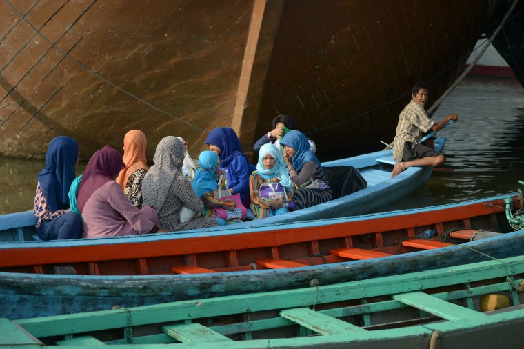 Indonesian muslim people ride a boat after attending Eid Al-Adha prayers at the Sunda Kelapa port in Jakarta on October 5, 2014. Muslims in Indonesia celebrated the day of sacrifice or Eid Al-Adha where people hold prayers and slaughter livestock as obligation to God's order. (Adek Berry/Getty Images)