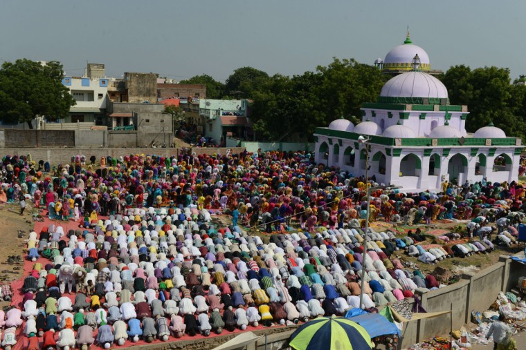 Indian Muslim men and women perform Special Prayers marking the end of the hajj pilgrimage to Mecca and welcoming the Eid al-Adha or the Feast of the Sacrifice, at the Shrine of Abdul Latif Mohammadshah (in front) and the Shrine of Hazrat Burhanuddin Kutbe Alam (Behind) in Vatwa area of Ahmedabad on October 5, 2014. Indian Muslims will celebrate Eid-al-Adha across India, tomorrow. (Sam Panthaky/Getty Images)