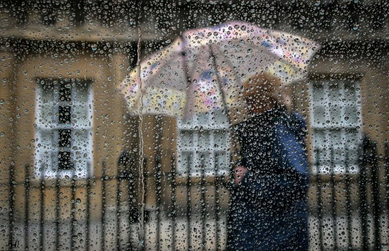 A woman passes a window covered in rain drops on October 6, 2014 in Bath, England. After one of the warmest and driest September months in recent years, the weather for October has turned much more autumnal, with a period of unsettled weather forecasted bringing much more wet and windy conditions to the UK. (Matt Cardy/Getty Images)