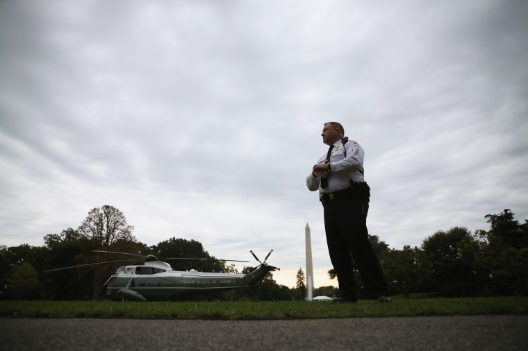 A member of the U.S. Secret Service stands guard as Marine One carrying U.S. President Barack Obama prepares to take off from the South Lawn of the White House October 7, 2014 in Washington, DC. Obama is traveling to New York to attend high ticket fundraisers for the Democratic Party. (Mark Wilson/Getty Images)