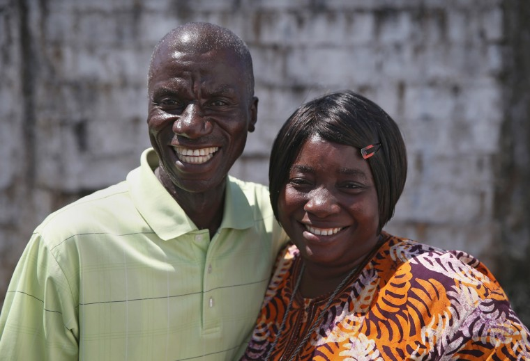 Ebola survivors Anthony Naileh, 46, and his wife Bendu Naileh, 34, stand at the Doctors Without Borders (MSF), Ebola treatment center after meeting with fellow survivors on October 16, 2014 in Paynesville, Liberia. Anthony said he is a steographer at the Liberian Senate and plans to go back to work for the January session. Bendu, a nurse, said she thought she caught Ebola after laying her hands in prayer on a nefew who had the disease in August. She then sickened her husband, who cared for her. The virus has a 70 percent mortality rate, according to the World Health Organization, but leaves survivors immune to the strain that sickened them. (Photo by John Moore/Getty Images)