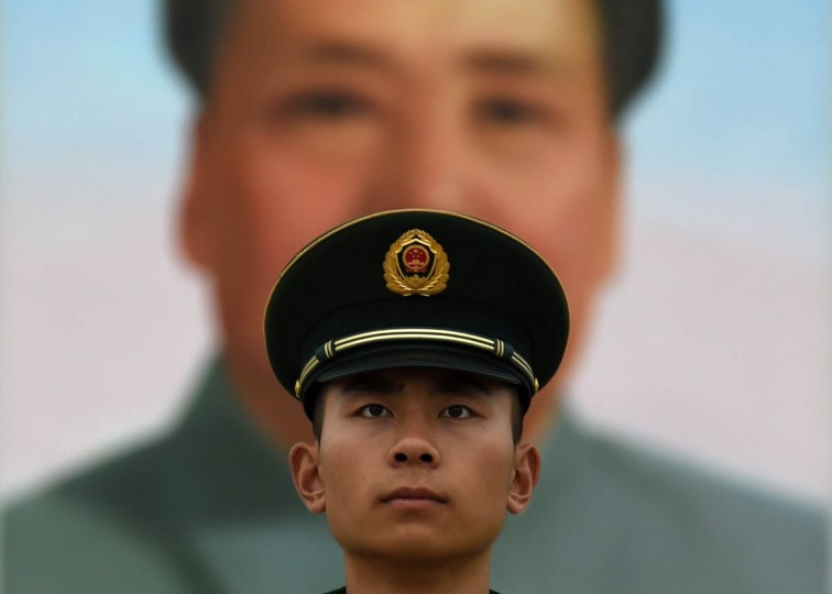 A paramilitary police officer stands guard in front of the portrait of late communist leader Mao Zedong on Tiananmen Gate in Beijing on China's National Day. Crowds visited the square on the 65th anniversary of the founding of Communist China, by late revolutionary leader Mao Zedong. (Greg Baker/Getty Images)