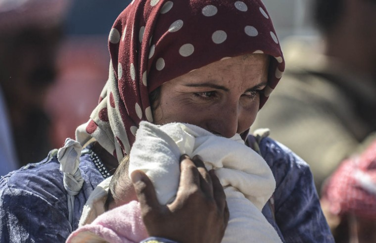 A Syrian Kurdish cries as she holds her baby in the southeastern town of Suruc in the Sanliurfa province after crossing the border between Syria and Turkey. Tens of thousands of Syrian Kurds flooded into Turkey fleeing an onslaught by the Islamic State (IS) group that prompted an appeal for international intervention. Some of the refugees now want to return to protect their homes and join the fight against IS militants. (Bulent Kilic/Getty Images)