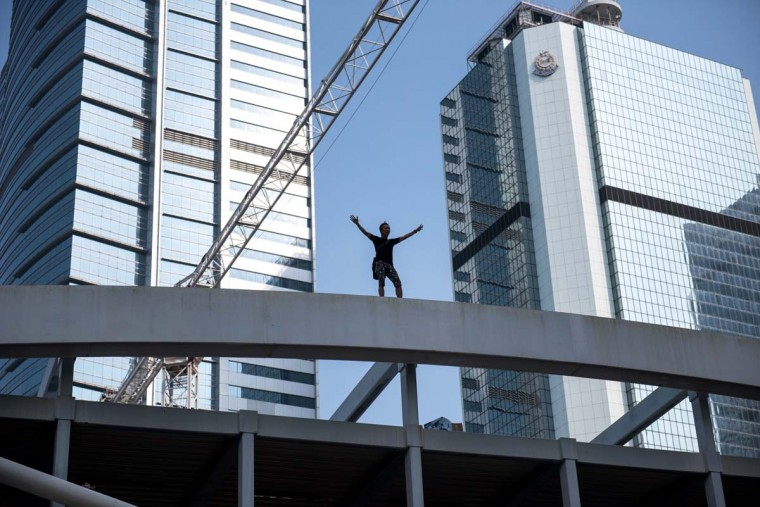 A man standing on top of a bridge overlooking a pro-democracy protest area shouts at onlookers and threatens to jump, near the central government offices in Hong Kong on October 5, 2014. Fresh clashes broke out at Hong Kong's pro-democracy protests on October 5, with riot police using batons and pepper spray to fight back demonstrators, as student leaders reopened the door to talks with the government. (Alex Ogle/AFP/Getty Images)