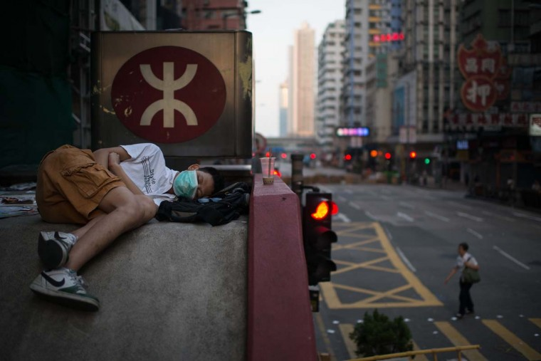 A pro-democracy protester sleeps on the roof of an MTR station as others occupy a street in the Mong Kok district of Hong Kong early on October 6, 2014. Pro-democracy demonstrators stood divided over whether to withdraw from protest sites across Hong Kong Sunday, hours before a government deadline to clear key roads they have blockaded for the last week. (Ed Jones/AFP/Getty Images)