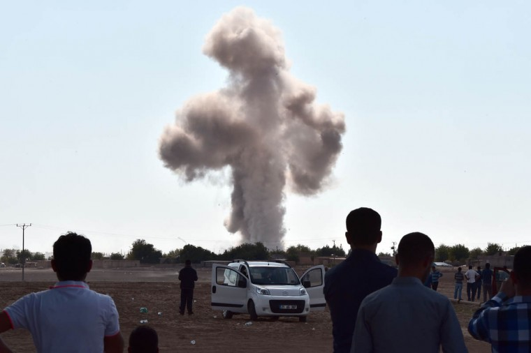 Smoke rises following an air strike on the western sector of the Syrian town of Ain al-Arab, known as Kobane by the Kurds, as seen from the Turkish-Syrian border, in the southeastern town of Suruc, Sanliurfa province, on October 8, 2014. Jihadists from the Islamic State group withdrew from some parts of the embattled Syrian town of Kobane overnight after air strikes by a US-led coalition, a monitor said. IS began its advance on Kobane, Syria's third biggest Kurdish town, on September 16, quickly sweeping through the surrounding countryside and prompting an estimated 186,000 people to flee the region across the border into Turkey. (Aris Messinis/Getty Images)