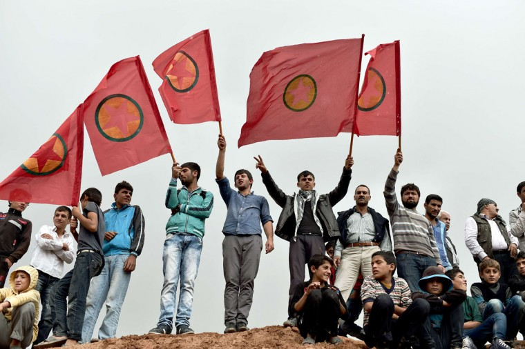 Kurdish people wave Kurdistan Workers' Party (PKK) flags while attending a funeral ceremony for YPG (People's Protection Units) fighters in the town of Suruc, Sanliurfa province, on October 14, 2014. (ARIS MESSINIS/AFP/Getty Images)