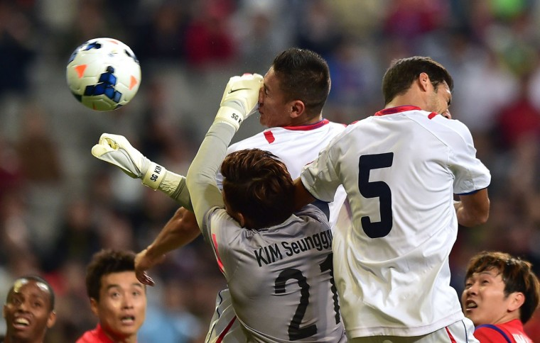 Costa Rica defender Oscar Duarte (center) heads a goal against South Korean goalkeeper Kim Seung-Gyu (bottom) during a friendly soccer match in Seoul on October 14, 2014. (JUNG YEON-JE/AFP/Getty Images)