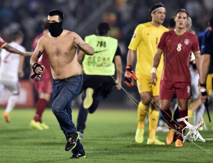 A masked Serbian supporter pulls a drone after a flag with Albanian national symbols was flown over the pitch and pulled down by Serbia's players during the EURO 2016 group I football match between Serbia and Albania in Belgrade on October 14, 2014. (AFP PHOTO/Getty Images/Andrej Isakovic)