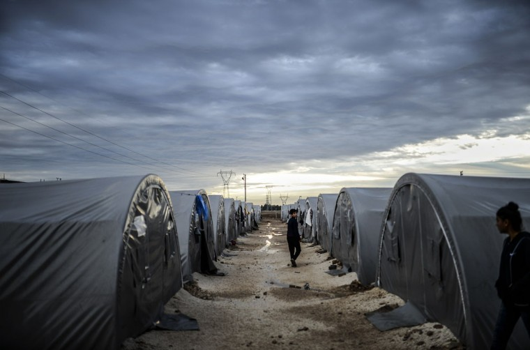 Kurdish people walk in a refugee camp early in the morning in the town of Suruc, Sanliurfa province, on October 19, 2014. (BULENT KILIC/AFP/Getty Images)