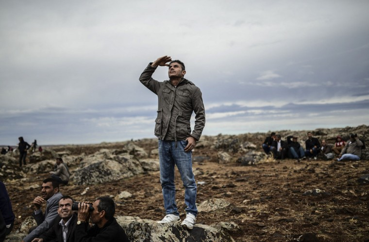 Kurdish people watch jet fighters fly over the Syrian town of Ain al-Arab, known as Kobane by the Kurds, from the Turkish border in the southeastern village of Mursitpinar, Sanliurfa province, on October 19, 2014. (BULENT KILIC/AFP/Getty Images)