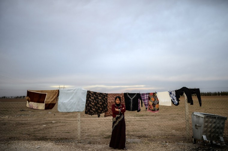 A Syrian Kurdish woman stands on October 23, 2014, in the Rojava refugee camp at Suruc in Sanliurfa province. Turkey said on October 21 that Kurdish peshmerga fighters based in Iraq have yet to cross into Syria from Turkish territory, a day after announcing it was assisting their transit to join the battle for the Syrian town of Kobane, also known as Ain al-Arab. It was seen as a major switch in policy by Turkey, which until now has refused to interfere in the over month-long battle for Kobane between Syrian Kurdish fighters and Islamic State (IS) jihadists. (BULENT KILIC/AFP/Getty Images)