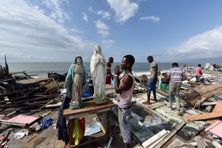 A man prays at the statue of the Virgin Mary amongst the debris of hundreds of destroyed homes, bulldozed during a clean-up operation of the coastal commune of Port Bouet, just east of Abidjan and west of Grand-Bassam, on October 23, 2014. (SIA KAMBOU/AFP/Getty Images)