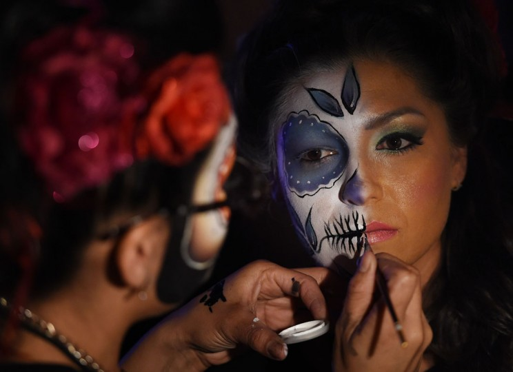 People rehearse their makeup for the upcoming festival of Dia de los Muertos at the Hollywood Forever Cemetery in Los Angeles, California on October 24, 2014. The Mexican festival celebrated on November 1, is held to remember friends and family members who have died and dates back to an ancient Aztec festival dedicated to the goddess Mictecacihuatl. (Mark Ralston/AFP/Getty Images)