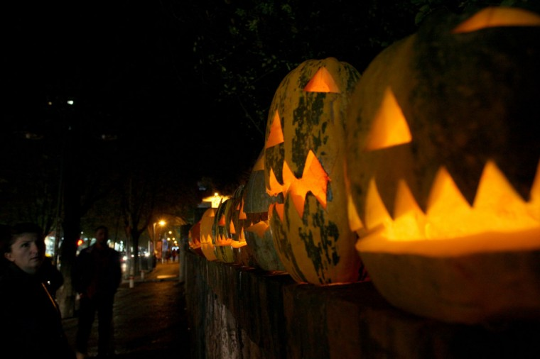 A customer looks at pumpkins carved as grimacing faces with candles inside in a street of Tirana on October 30, 2014, one day before Halloween. (Gent Shkullaku/AFP/Getty Images)