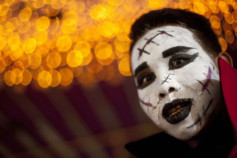 A man with costume make up looks on at a Halloween party in Yangon on October 31, 2014. Halloween, a contraction of All Hallows' Eve, is celebrated on the last day of October before All Saints Day. The tradition of revellers dressing up as ghosts during Halloween goes back to a folk belief that beings from the afterlife will mingle with those on earth on that day, thus humans disguised as ghosts will be left alone by the supernatural. (Ye Aung/AFP/Getty Images)