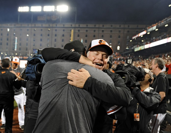 Orioles manager Buck Showalter, right, hugs Adam Jones on the field after the O's clinched the American League East division by defeating the Blue Jays in September 2014. (Kenneth K. Lam/Baltimore Sun)