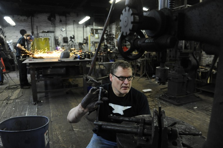 Peter Krug, owner of G. Krug & Son Ironworks, lines up a drill press to make points on window pickets. The drill press is from the early 1900s. (Kim Hairston/Baltimore Sun)