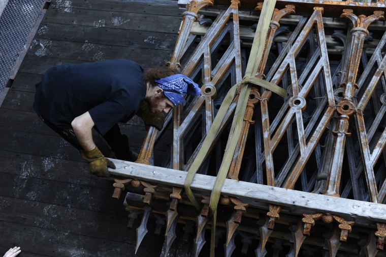 Evan Price of Reservoir Hill, a fabricator for G. Krug & Son Ironworks, works to move fencing from the Washington Monument in Mount Vernon Place into the shop for repairs. (Kim Hairston/Baltimore Sun)