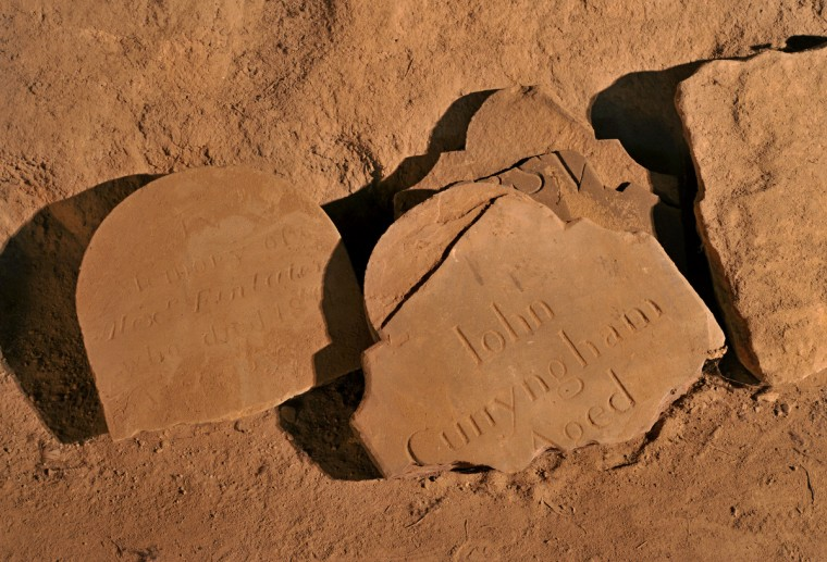 Fragments of tombstones rest on the dirt floor of the catacombs, protected from the elements that have weathered the above ground grave markers. Other tombstones for the Cunyngham family are outside. Amy Davis / Baltimore Sun